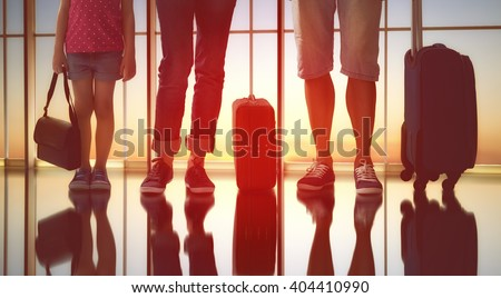 Happy family with suitcases in the airport.  - stock photo