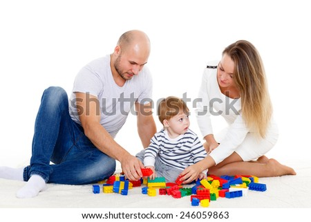 Happy family with sweet baby play on a white background. Early development and learning toys.
