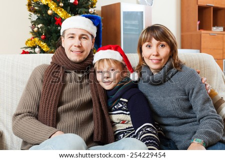 Happy family with teenage son at home with  Christmas tree at home - stock photo