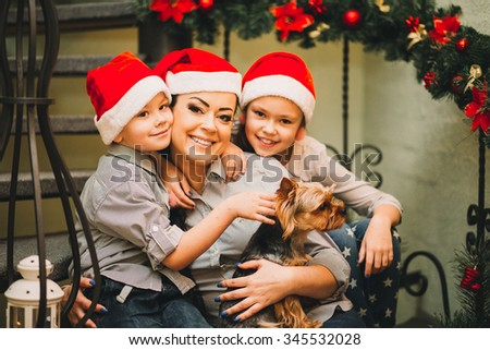 happy family with the dog at Christmas and New Year with gifts around the Christmas tree. in Christmas red hat and same clothes, Happy mother and son, daughter - stock photo