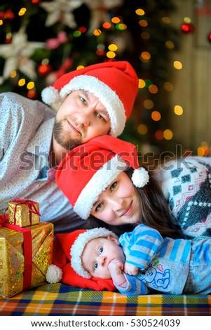 Happy family with the newborn son in santa clauss caps lie on a floor near