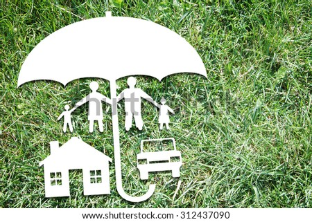 Happy family with their property under protection on backdrop of green grass. Abstract conceptual image - stock photo