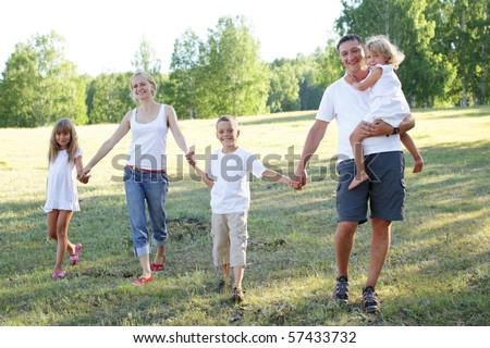 Happy family with three children walking on park