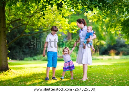 Happy family with three kids in a park. Young mother with children, little toddler girl, school age boy and baby playing in a sunny summer garden, walking and holding hands with her son and daughter. - stock photo