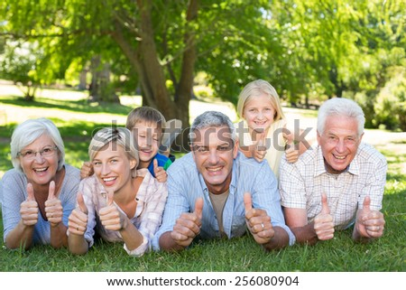 Happy family with thumbs up on a sunny day - stock photo