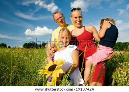 Happy family with tree kids standing in a field of wild flowers together - metaphor for love - stock photo