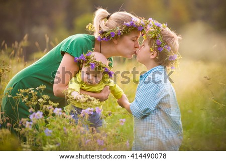 Happy family with two boys on a summer meadow. Mother with adorable kid boy and cute baby in flower wreath. Family together, parent with little children. Woman kissing children on sunny day. - stock photo