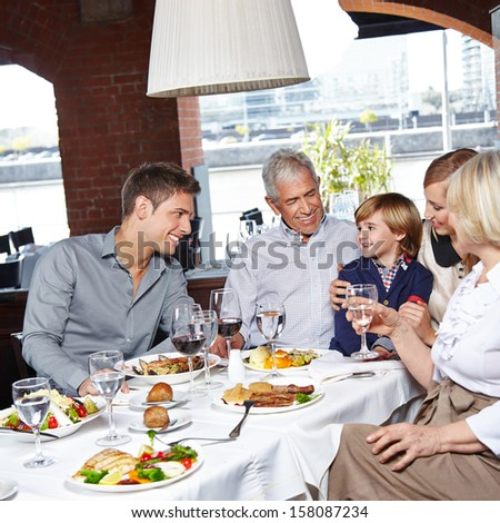 Happy family with two children and grandparents eating in a restaurant - stock photo