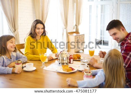 Happy family with two children having breakfast in the kitchen of their house