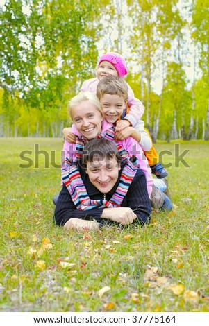 Happy family with two children in autumn park