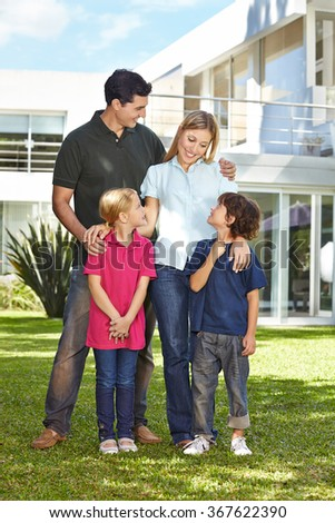 Happy family with two children in front of a modern house