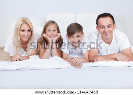 Happy Family With Two Children Lying On Bed At Home - stock photo