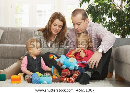 Happy family with two children playing on floor in living room at home sitting on floor in front of sofa. - stock photo