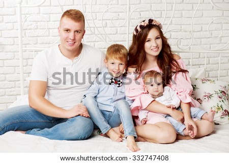 Happy family with two children sitting on the bed
