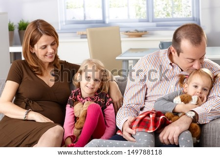 Happy family with two daughters and pregnant mother sitting on sofa at home, smiling. - stock photo