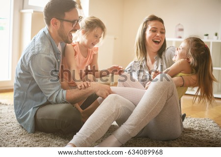 Happy family with two daughters playing at home. Family sitting on floor and playing together.