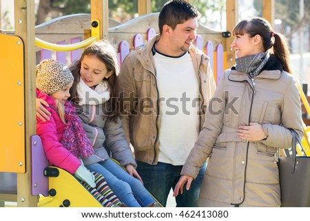 Happy family with two girls at sliding board outdoors