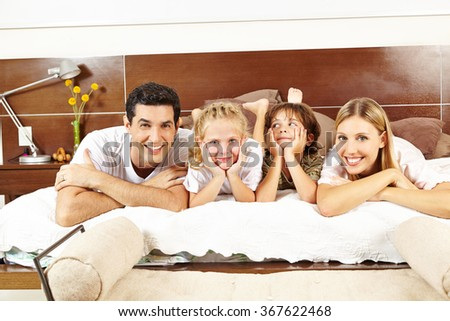 Happy family with two kids laying together on bed in bedroom