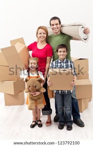 Happy family with two kids moving to a new house carrying their stuff