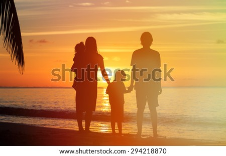 happy family with two kids on sunset tropical beach - stock photo