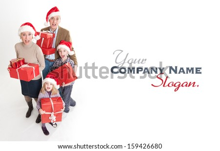 Happy family with two kids wearing Santa  hats carrying presents