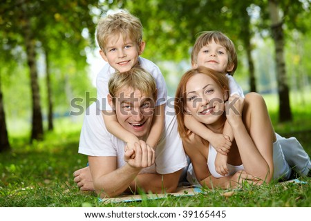 Happy family with two sons frolic on a lawn - stock photo