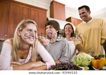Happy family with two teenage children making funny faces in kitchen - stock photo