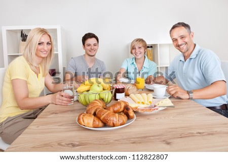 Happy family with two teenage children sitting around the table enjoying a healthy breakfast