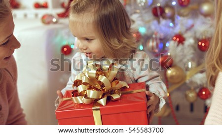 Happy family with two young daughters at the Christmas tree with gifts