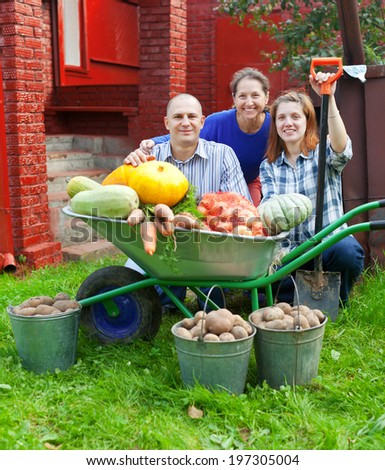 Happy  family with vegetables harvest in garden - stock photo