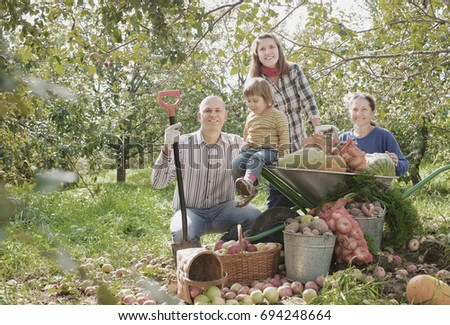 Happy  family with vegetables harvest in garden