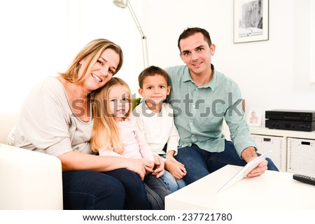 Happy family with young kids at home playing with a digital tablet in sofa - stock photo