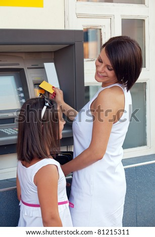 Happy family withdrawing money from credit card at ATM - stock photo