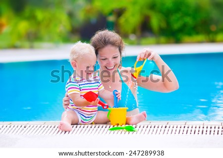 Happy family, young active mother and adorable curly little baby having fun in a swimming pool, playing with toy watering can and shovel, enjoying summer vacation at a tropical resort