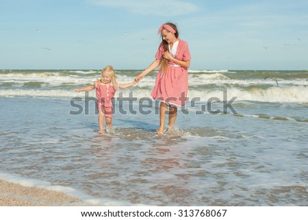 Happy family. Young beautiful  mother and her daughter having fun on the beach. Positive human emotions, feelings, joy.