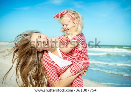 Happy family. Young beautiful  mother and her daughter  having fun on the beach. Positive human emotions, feelings. - stock photo