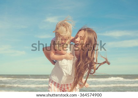 Happy family. Young beautiful  mother and her daughter  having fun on the beach. Positive human emotions, feelings. Retro toned - stock photo