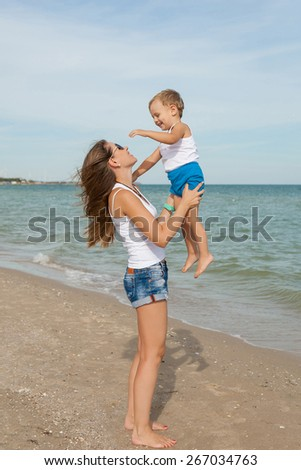 Happy family. Young beautiful  mother and her son having fun on the beach. Positive human emotions, feelings, joy.