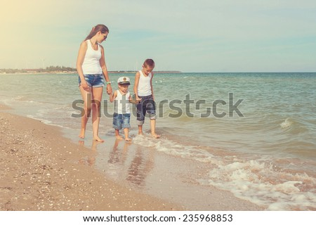 Happy family. Young beautiful  mother and her two sons having fun on the beach. Positive human emotions, feelings, joy.