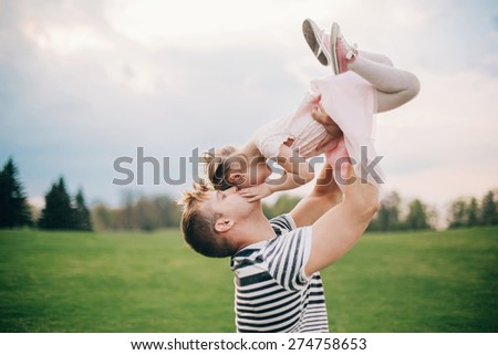 Happy family. Young father playing silly with his daughter lifting her up