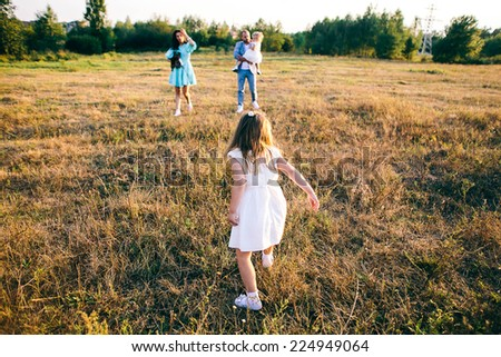 Happy family: young father with his little children walking in the field in summer morning. - stock photo
