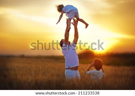 Happy family: young father with his little children walking in the wheat field at summer sunset. Strong healthy daddy abandoning his daughter against beautiful flaming sky. - stock photo