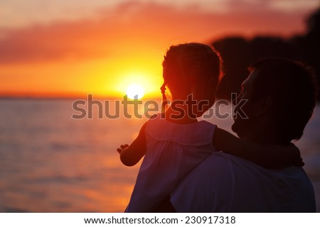 Happy family: young father with his little daughter walking along the sea coast at summer sunset. Strong healthy daddy talking to his daughter against beautiful flaming sky.  - stock photo