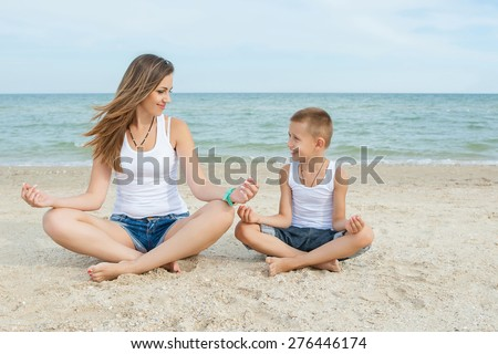 Happy family. Young happy beautiful  mother and her son doing yoga on coast of sea on beach - stock photo