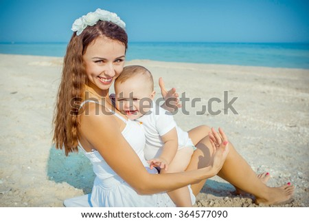 Happy family. Young happy beautiful  mother and her son having fun on the beach. Positive human emotions, feelings. - stock photo