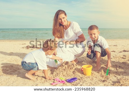 Happy family. Young happy beautiful  mother and her two sons having fun on the beach. Positive human emotions, feelings, emotions. - stock photo