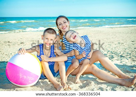 Happy family. Young happy beautiful  mother and her two sons having fun on the beach. Positive human emotions, feelings.
