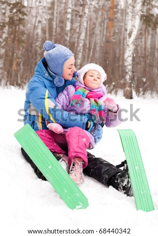 happy family; young mother and her daughter skiing and having fun in the winter park (focus on the child) - stock photo