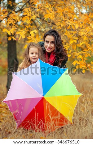 Happy family: young mother and her little daughter with a multi-colored umbrella. Woman and child playing and cuddling at autumn park. Nature walks outdoors.  - stock photo