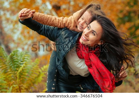 Happy family: young mother and her little daughter. Woman and child playing and cuddling at autumn park. Nature walks outdoors.  - stock photo